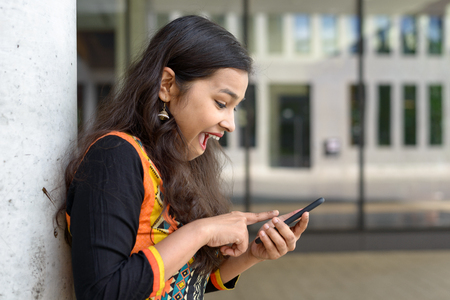 Excited young Indian girl exclaiming at a sms or text message on her mobile phone as she receives good news while relaxing leaning against a wall outdoors