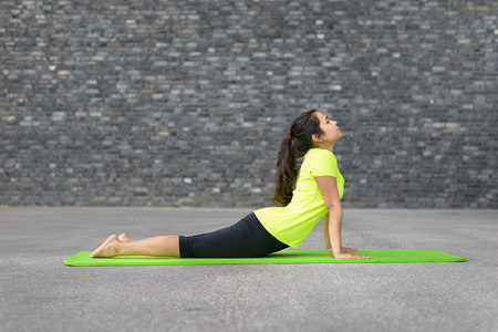 Fit athletic young woman doing yoga exercises stretching and arching her back with raised arms in a profile view on a mat in front of the wall of an urban building with copy space Stock Photo