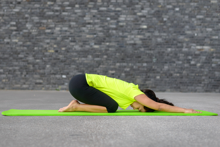 Supple young woman working out with yoga on a mat in front of a grey brick wall in an urban environment in an active lifestyle concept
