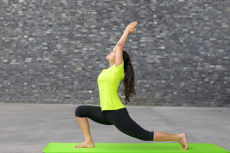 sanskrit: Fit athletic young woman doing yoga exercises stretching and arching her back with raised arms in a profile view on a mat in front of the wall of an urban building with copy space Stock Photo