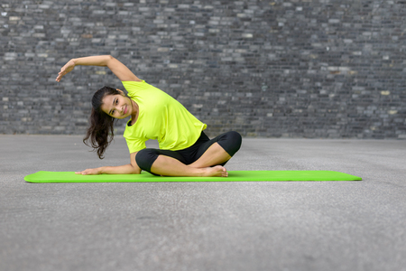 Portrait of young woman relaxing while practising yoga pose, Sitting Side bend