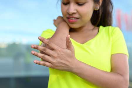 Young woman holding painful elbow during exercising outdoors