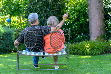Senior Couple Sitting On A Wrought Iron Garden Bench In The Shade Of A Tree  With