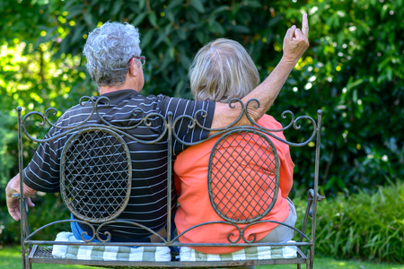 Senior couple sitting on a wrought iron garden bench in the shade of a tree with their backs to the camera admiring the lush green vegetation with the man making a rude gesture