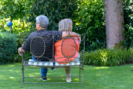 Elderly couple sitting in a lush green garden on a wrought iron bench in the shade of a tree with their backs to the camera in an affectionate embrace