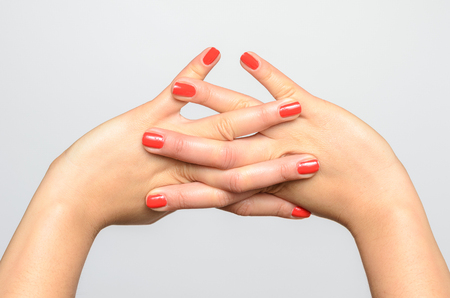 nails: Female hands with red nails crossed against white background Stock Photo