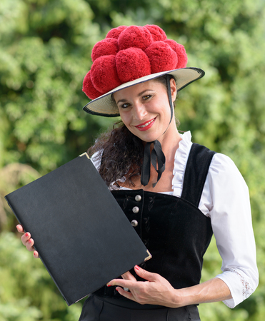 A portrait of a beautiful german waitress holding a menu in traditional clothing wearing a bollenhut.