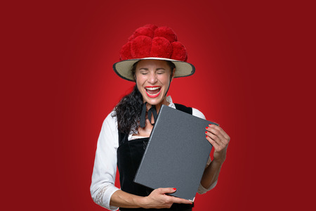 Candid portrait of a laughing attractive young Black Forest waitress holding a menu dressed in traditional clothes with a Bollenhut decorated with red pompoms over a matching background with copyspace Stock Photo