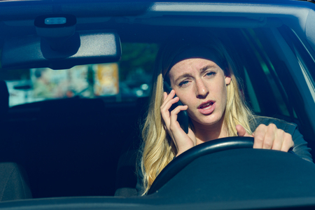 Front view of young blond woman talking on phone while driving car Stock Photo