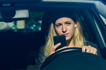 Young blond woman using mobile phone while driving car Stock Photo