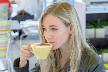 Young blond woman sipping cup of coffee at cafe Stock Photo