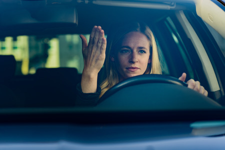 Front view of young frustrated blond woman driving car