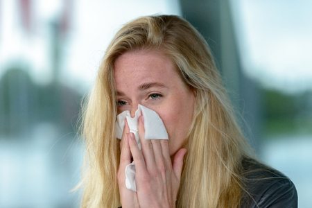 Portrait of young blond woman blowing her nose into tissue, while having her eyes opened. Reklamní fotografie