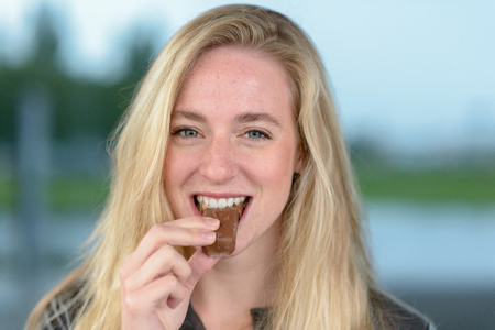 Portrait of young cheerful blond woman eating chocolate