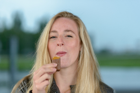 Portrait of young smiling blond woman eating chocolate