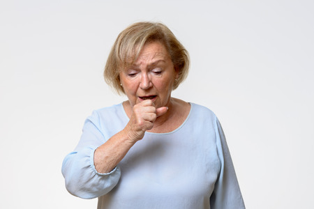 Distressed senior woman coughing holding her hand politely in front of her mouth in a front view on grey with copy space Stock Photo