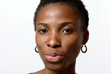 Pretty young African woman pouting her lips and looking to the camera.