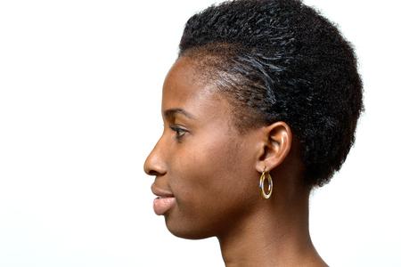 静かな笑顔と白空白のコピー スペースを直面しているきちんとした短い髪型で魅力的なアフリカ女性の横顔の肖像画 写真素材