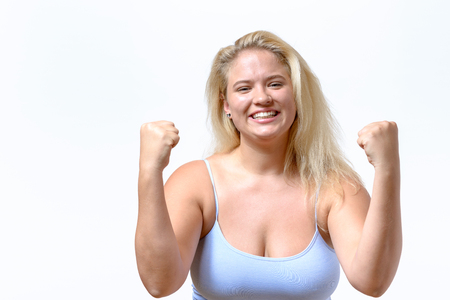 Enthusiastic jubilant young woman showing her elation punching the air with her fists after a victory or success isolated on white