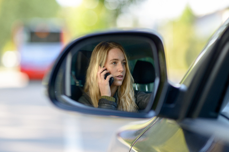 Young blonde female driver reflecting in car wing mirror while phoning