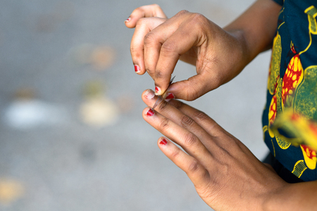 Young African woman doing her fingernails outdoors shaping the trendy red varnish or lacquer in a close up view with copy space Stock Photo