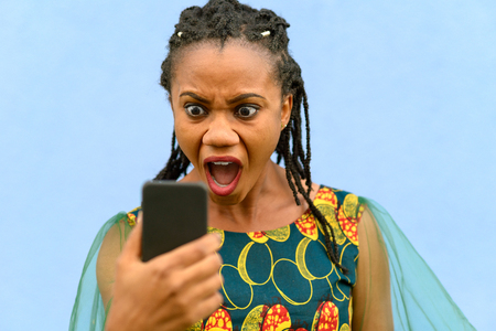 Horrified upset young African American woman in a stylish dress gawping wide eyed at her mobile phone isolated over blue