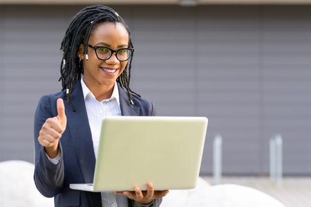 Portrait of cheerful elegant African American woman with laptop giving thumb up Stock Photo