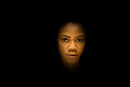 Mysterious night portrait of a pretty young African woman with a serious expression surrounded by complete darkness as though floating or disembodied Stock Photo