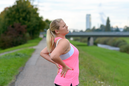 Young blonde woman wearing sportswear holding her painful back while exercising outdoors Фото со стока