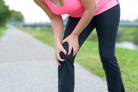 Woman wearing sportswear holding her painful knee while exercising outdoors Фото со стока