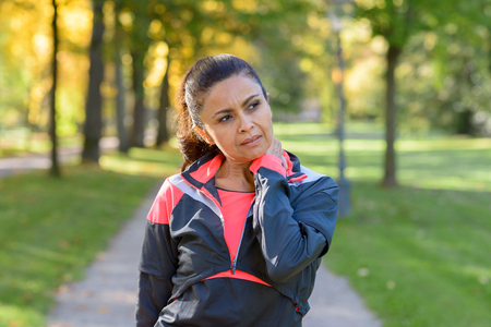 Adult woman holding her painful neck after exercising in park and looking to the side Stock Photo