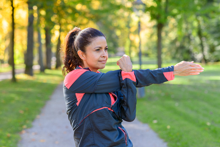 Adult woman wearing sportswear stretching her arm to the side on sunny day