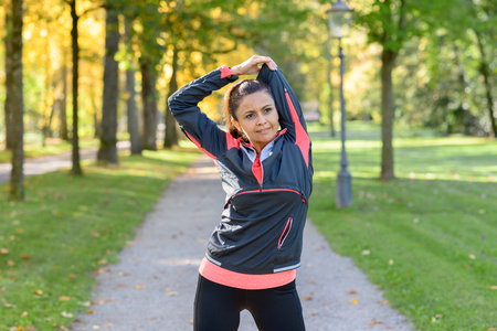 Adult woman wearing sportswear stretching in park on sunny day Stock Photo