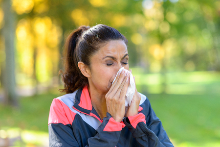 Woman blowing her nose on a tissue outdoors in a leafy green park while out jogging conceptual of seasonal flu or allergies Stock Photo