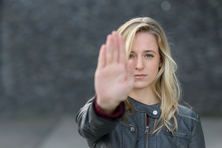 Stern young woman making a stop gesture with her raised hand as she stands outdoors with focus to her face and copy space