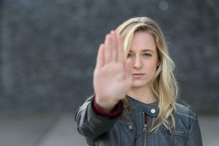 Popa mujer joven haciendo un gesto de parada con su mano levantada mientras se encuentra al aire libre con enfoque en su rostro y copia espacio