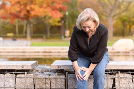彼女はコピースペースで秋の日に歩いて自分自身を負傷した後に池の周りの壁に座っているように痛みで彼女の膝をつかむ年配の女性 写真素材