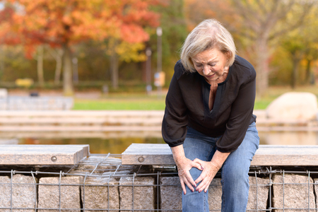 Elderly lady grabbing her knee in pain as she sits on a wall surrounding a pond after injuring herself out walking on an autumn day with copy space Banque d'images
