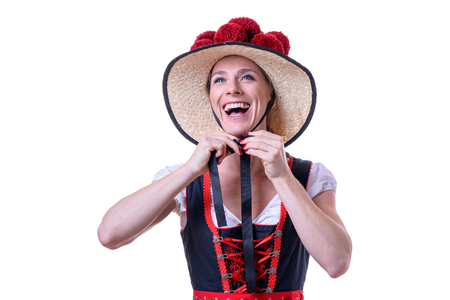 Attractive young woman binding her Black Forest traditional dress with a Bollenhut adorned with 14 red pompoms Stock Photo