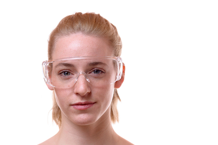 Front view close-up portrait of a beautiful young woman wearing safety glasses for protection against white background for copy space