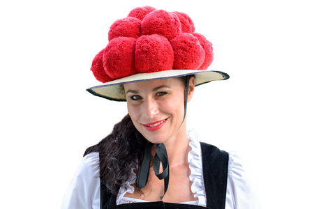 Attractive young woman wearing a traditional Black Forest Bollenhut with its 14 pompoms as she smiles at the camera, before white background