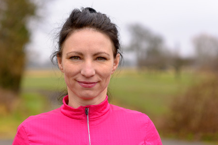 Attractive woman with a quiet friendly smile wearing a bright pink top standing outdoors on a winter day in the countryside in a head and shoulders portrait Stock Photo