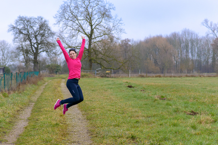 Agile athletic woman leaping in the air with her arms raised on a farm road on a grey dismal winter day