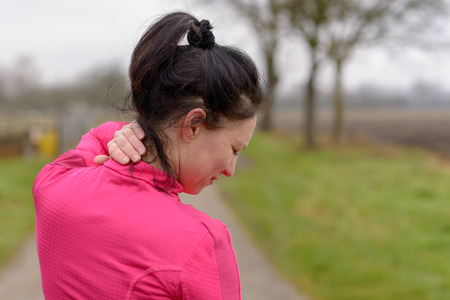 Woman clutching her neck in pain while out exercising on a country road in winter in a close up cropped view