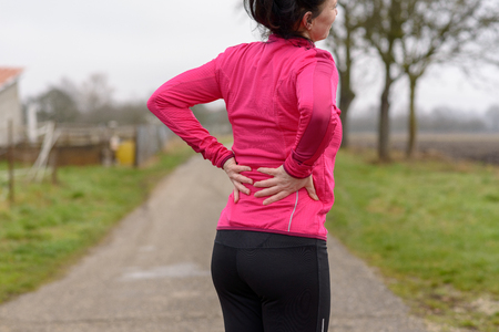 Woman with back or kidney pain clutching her lower back as she takes a break from jogging or working out on a rural road in winter in a close up cropped view