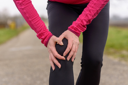 Woman jogger clutching her injured knee with a grimace of pain as she pauses during her workout on a country road in winter in a close up cropped view