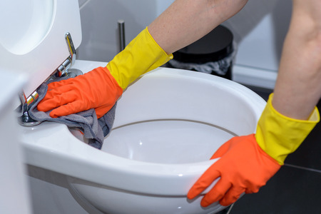 Person wearing orange rubber gloves wiping out a toilet bowl with a cloth in a household chores and hygiene concept
