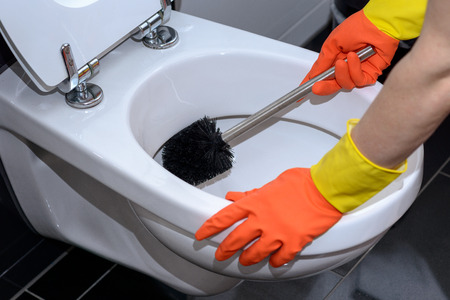 Woman in orange gloves cleaning out the toilet bowl with a brush to remove germs and bacteria under the rim in a concept of cleanliness, hygiene and household chores