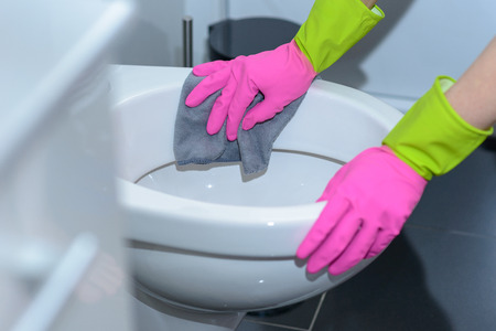Person wearing colorful bright pink rubber gloves wiping out a toilet bowl with a cloth in a household chores and hygiene concept
