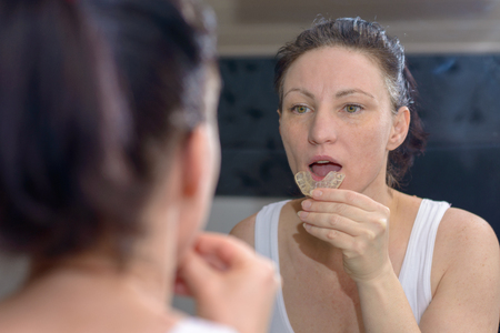 Woman holding an upper bite plate to prevent grinding her teeth together as she looks at her reflection in the mirror